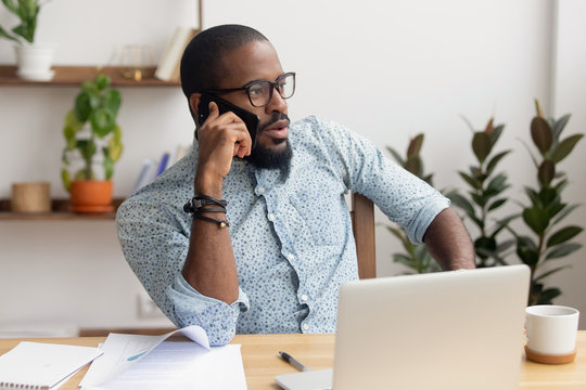 Serious african businessman talking on phone sitting at office desk