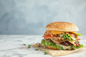 Tasty burger with bacon on table against color background. Space for text