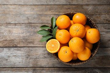 Fototapete - Wicker bowl with ripe oranges on wooden background, top view. Space for text