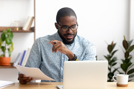 Focused african american businessman working with laptop documents in office