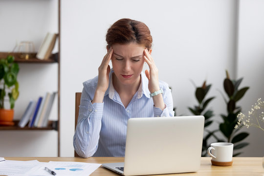 Tired frustrated businesswoman coping with strong headache attack at workplace