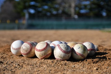 Close-up photo of a bunch of game used baseballs on a baseball infield on a sunny day with a baseball field in the background