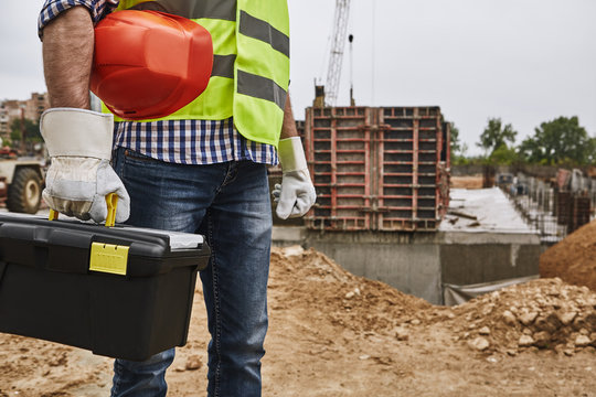 Ready to work! Cropped image of a builder in working uniform holding red helmet and carrying toolbox while standing at construction site