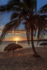 Rancho Luna caribbean beach with palms and straw umrellas on the shore, sunset view, Cienfuegos,...