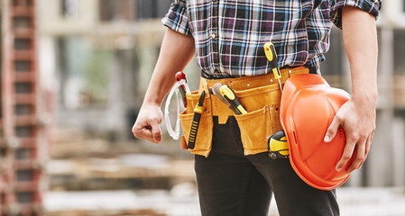 Safe work. Cropped photo of male professional builder with construction tools holding a safety red helmet while standing outdoor of construction site