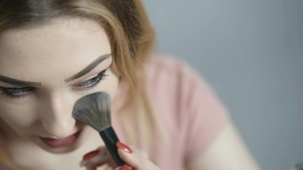 Wall Mural - girl blows off excess with a fluffy brush and admires in a mirror on a studio background, face of a young woman with make-up, beauty and cosmetics concept