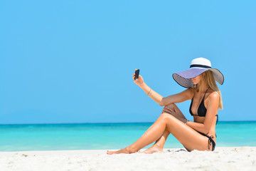 Cheerful young woman having fun taking smartphone selfie pictures of herself on tropical beach travel Caribbean holidays. Happy European girl model wearing fashion hat near sea. Summer lifestyle.