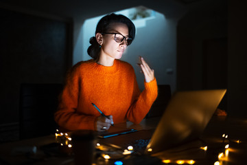 Portrait of young designer girl working at graphic tablet on laptop. Dressed in yellow wearing glasses.