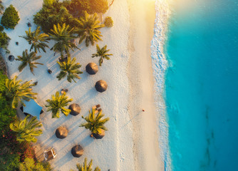 Printed kitchen splashbacks Zanzibar Aerial view of umbrellas, palms on the sandy beach of Indian Ocean at sunset. Summer holiday in Zanzibar, Africa. Tropical landscape with palm trees, parasols, white sand, blue water, waves. Top view