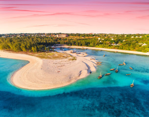 Poster Zanzibar Aerial view of the fishing boats on tropical sea coast with sandy beach at sunset. Summer holiday. Indian Ocean, Zanzibar, Africa. Landscape with boat, green trees, blue water, colorful sky. Top view