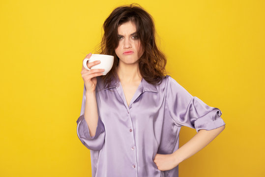 Annoyingly looking young girl with cup of coffee