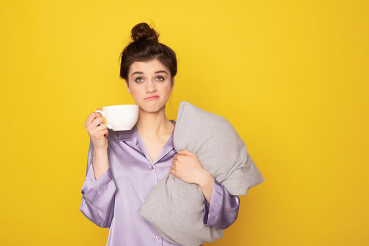 Annoyed girl with cup of coffee and pillow