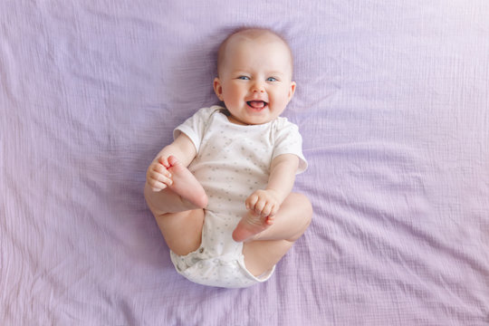 Portrait of cute adorable smiling laughing white Caucasian baby girl boy with blue eyes four months old lying on bed looking at camera. View from top above. Happy childhood lifestyle.