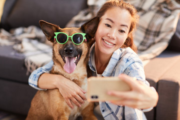 Portrait of smiling Asian woman taking selfie with dog wearing sunglasses, copy space