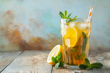 Traditional iced tea with lemon and ice in tall glass on a wooden rustic table. With copy space