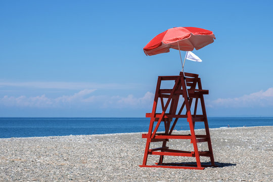 Red rescue tower and beach umbrella