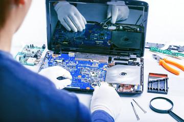 Computer Repair. Tech fixes motherboard in service center.