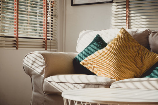 Close up pillow on sofa at home in morning with sunlight.Furniture in house background with light shade on object