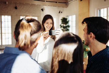 Young woman taking picture of group of friends in bright loft apartment using mobile phone camera