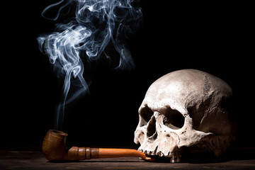 Close up portrait of human skull with smoking pipe and smoke on black background. Health danger concept