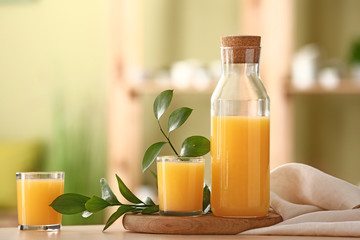 Bottle and glasses of tasty orange juice on table