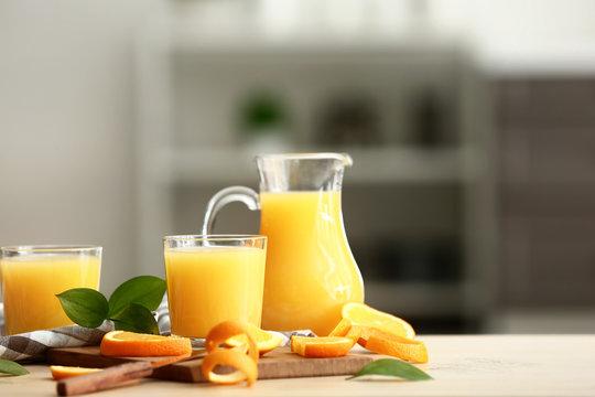 Tasty orange juice on table in kitchen