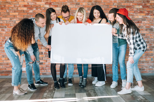 Joyful millennials holding blank whiteboard mockup. Young people laughing, looking at copy space for fun, amusing content.