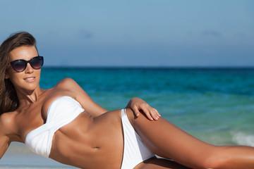 Woman in bikini laying by sea