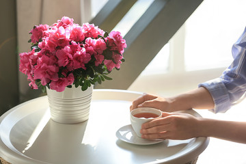 Spoed Foto op Canvas Azalea Woman drinking tea at table with beautiful blooming azalea