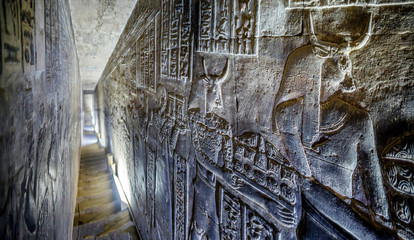 Dendera temple or Temple of Hathor Egypt. Corridor with relief images based on the mythology of ancient Egypt.