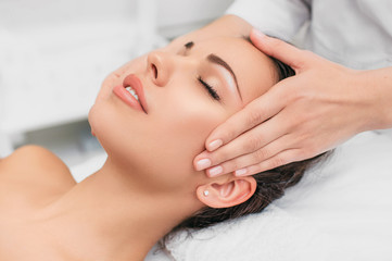 Beautiful woman enjoying in head massage during beauty treatment in the spa.