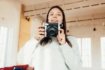 Young woman taking photo using big vintage camera at bright loft apartment