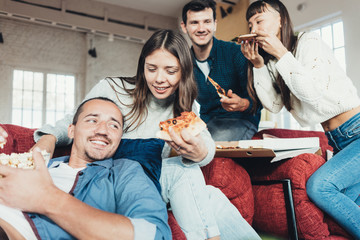 Group of friends at home party fooling and enjoying. Eating pizza, snacks, watching movies and talking. Bright sunny apartment