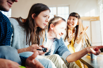 Group of friends playing video games together using controller in big bright apartment
