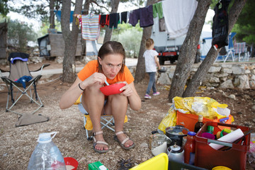 Mother with daughter at the campsite, preparing food in outdoor kitchen, having fun in the outdoors.