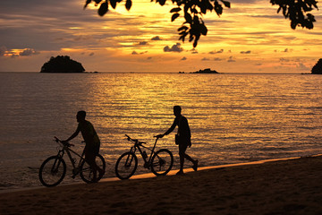 Wall Mural - Two cyclist relaxing and enjoyed beautiful sunset along the beach in pangkor island, perak malaysia
