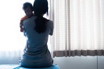 Photo of mother carrying her baby sick in dark room with light shine through curtain
