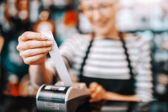 Close up of smiling Caucasian female worker with short blonde hair and eyeglasses using cash register while standing in bicycle store.