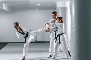 Young Caucasian highly motivated armless young woman kicking wooden board while two her friends from club holding it. Taekwondo class. Wall mural
