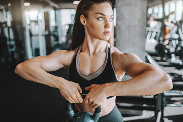 Pretty Caucasian female bodybuilder with ponytail lifting kettlebell. In background gym equipment. Motivate your mind, the body will follow.