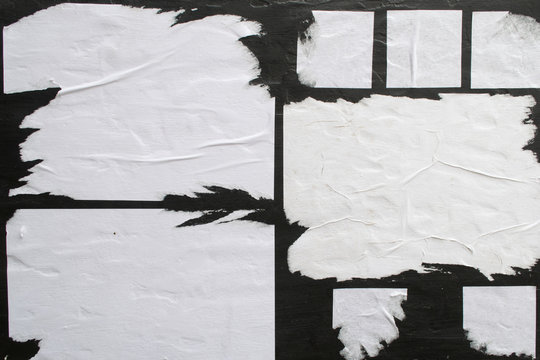 Several sheets of white paper pasted on a black wall.