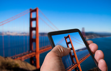 Tourist taking photo of Golden Gate Bridge in San Francisco, California on mobile gadget from top of a hill. Hand holding smartphone. Travel concept