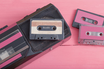 Old plastic cassette with tape recorder on wooden background. Retro music concept