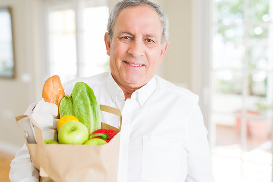Handsome senior man holding paper bag full of fresh groceries and smiling at home