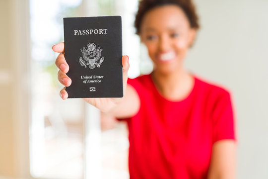 Young african american woman holding passport of United States of American with a happy face standing and smiling with a confident smile showing teeth