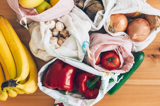 Zero Waste shopping concept. Fresh groceries in eco cotton bags on wooden table, flat lay. Vegetables from market in reusable bags. Ban single use plastic. Sustainable lifestyle