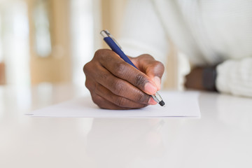Close up of african man writing a note on a paper