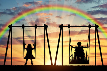 Happy child is a disabled person in a wheelchair riding an adaptive swing next to a healthy child together