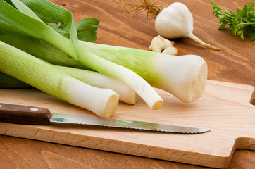 Leeks cut into slices on wooden plank on wooden background.