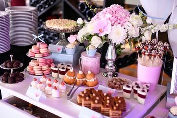 Delicious candy bar with cupcakes, cake pops, macaroons and other sweets